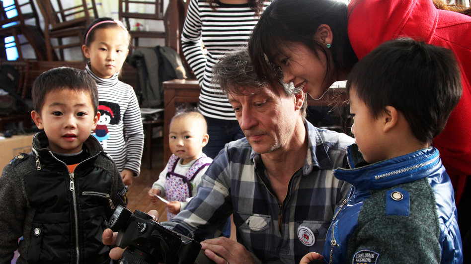 Lutz Michaelis, a robotics engineer from Germany, shows a Chinese family a preview of their free portrait last weekend in Shanghai. (NPR)