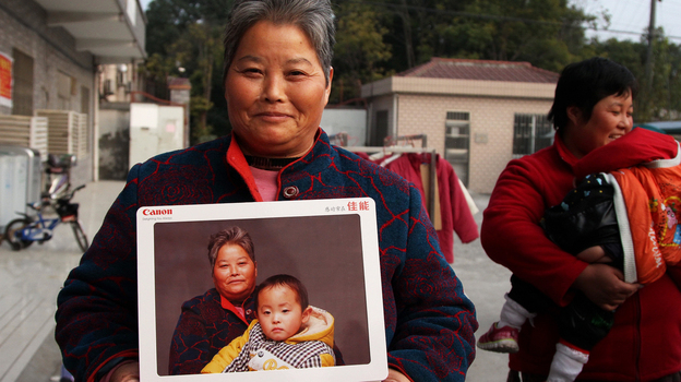 Zheng Jinrong poses with a portrait of herself and her grandson in a migrant village in Shanghai. She received the photographs as part of a global event to provide high-quality portraits for people who otherwise can't afford them. (NPR)