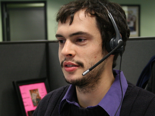 Joey Cappuccitti, who works at a Maximus call center, talks with a person looking for help with New York's insurance exchange.