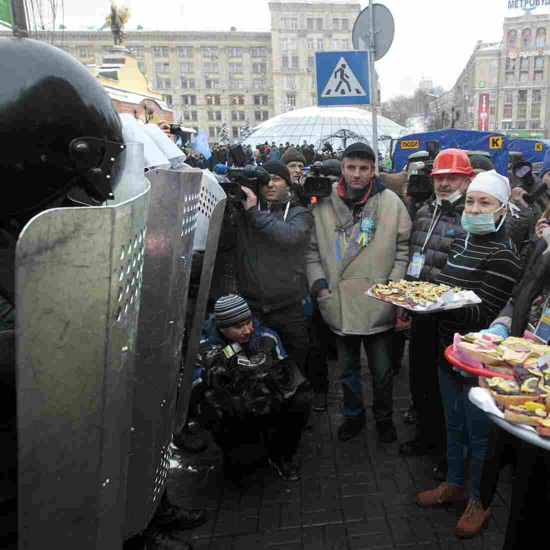 Activists who had backed Ukraine's plan to form closer ties to the European Union try to give food to riot police officers preparing to block the Independence Square in Kiev Monday.