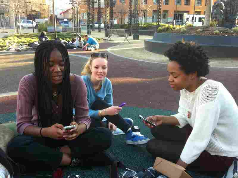 Three high school students in Oakland, Calif., swap photos using Snapchat.