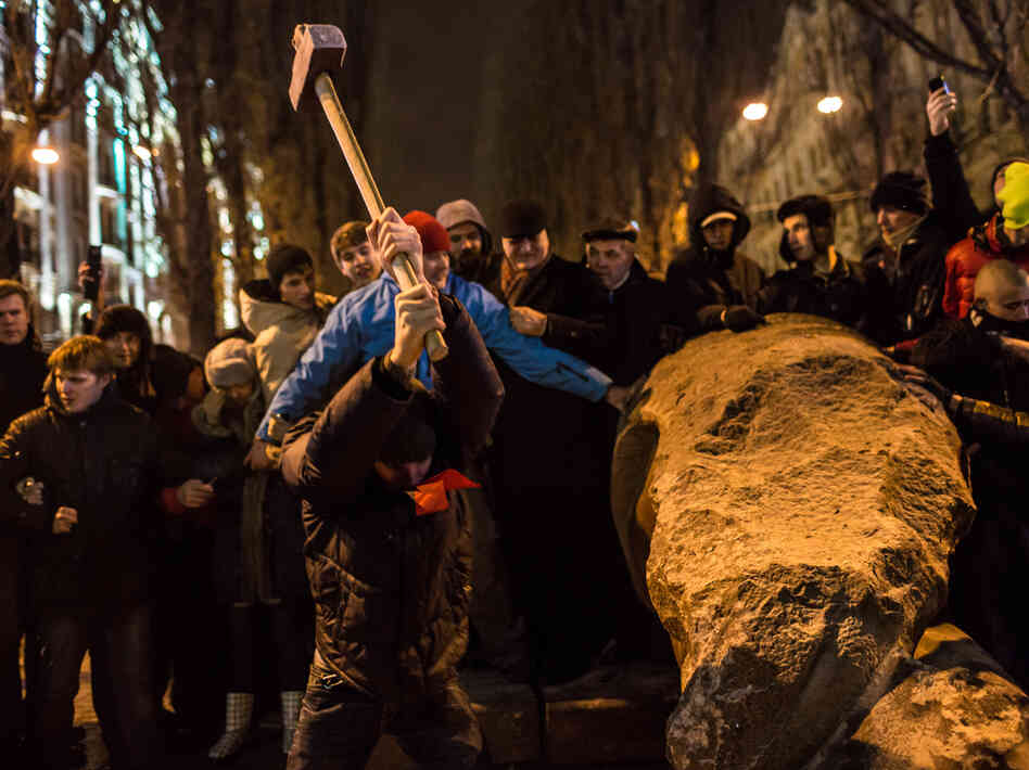 Anti-government protesters use a sledge hammer to destroy a statue of Russian communist revolutionar