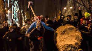 Anti-government protesters use a sledge hammer to destroy a statue of Russian communist revolutionary leader Vladimir Lenin on Sunday in Kiev.