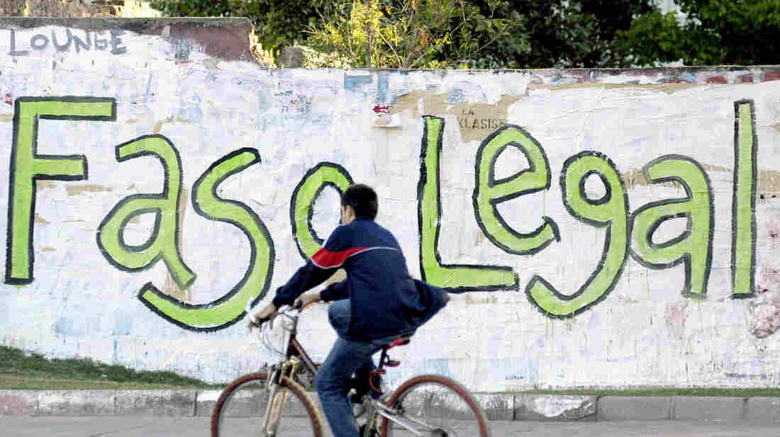 """A bicycle passes graffiti that reads in Spanish, """"Legal pot,"""" in Montevideo, Uruguay, in November 2012."""