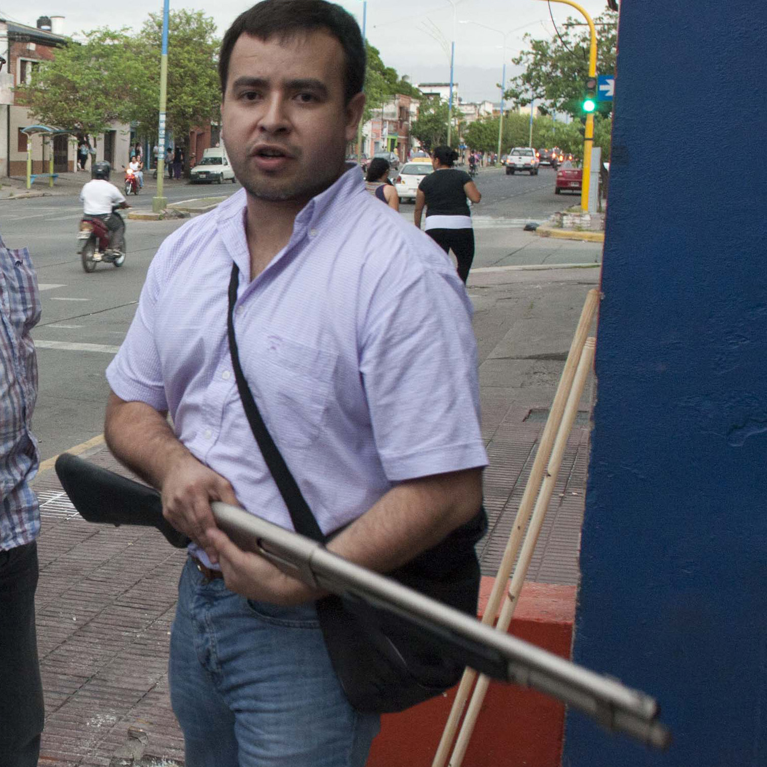 An armed shopkeeper stands outside his shop after it was looted in San Miguel de Tucuman, Argentina, on Monday. The country's government dispatched federal police to trouble spots as looting spread early this week.