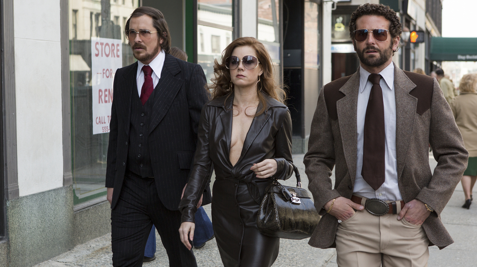 A '70s con-artist couple (Christian Bale and Amy Adams) are forced to team up with an FBI agent (Bradley Cooper, right) in American Hustle, inspired by a real-life sting targeting corrupt politicians. (Columbia Pictures)