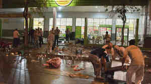 Supermarket employees try to recover items left by looters in San Miguel de Tucuman, Argentina, on Monday. Looting has spread across Argentina as mobs take advantage of strikes by police demanding pay raises to match inflation.