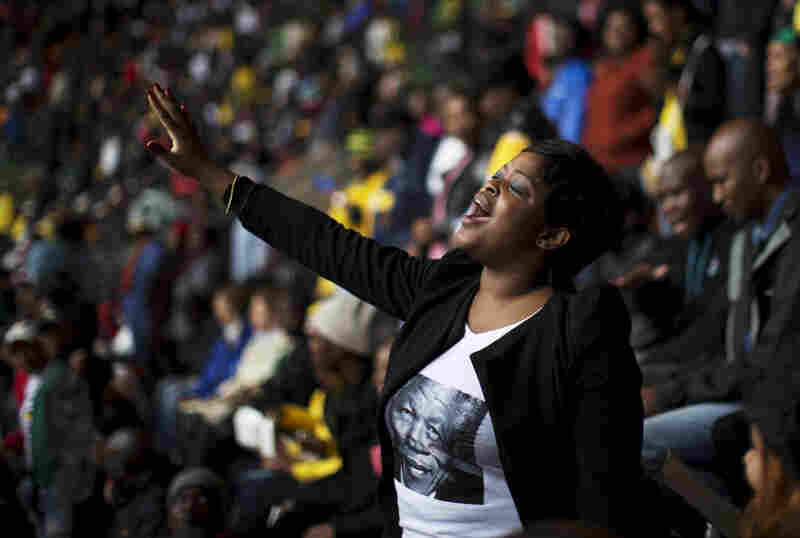"A woman sings in the stands. ""There is, of course, much music — some of it mournful and some of it joyful,"" Quist-Arcton reports. ""Either way, South Africans are dancing and swaying, with their umbrellas up."""