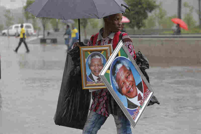 A man sells portraits of Mandela outside the memorial service.
