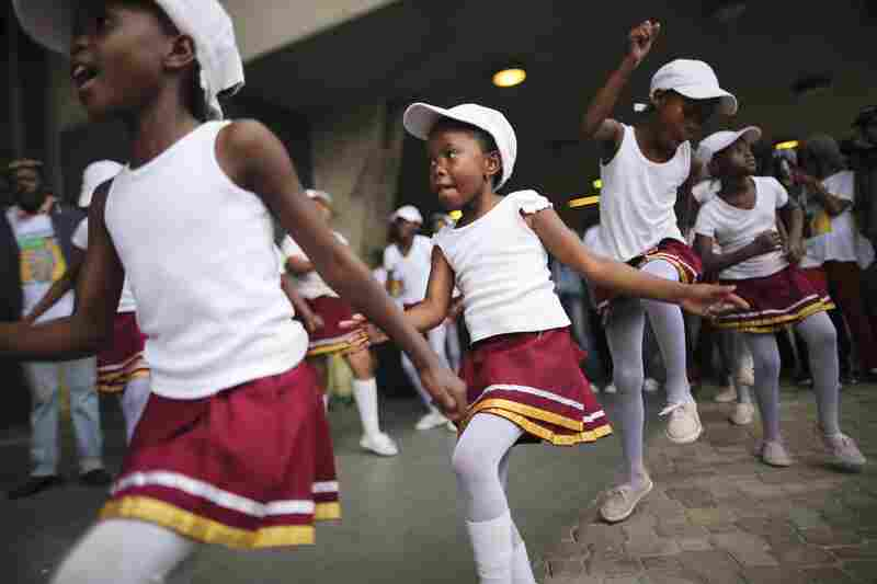 South African girls dance during the service. The memorial celebrated Mandela's gift for uniting enemies across political and racial divides.