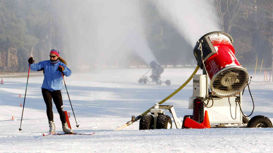 A skier glides past a snow-making machine pumping out snow in Weston, Mass., in 2010.