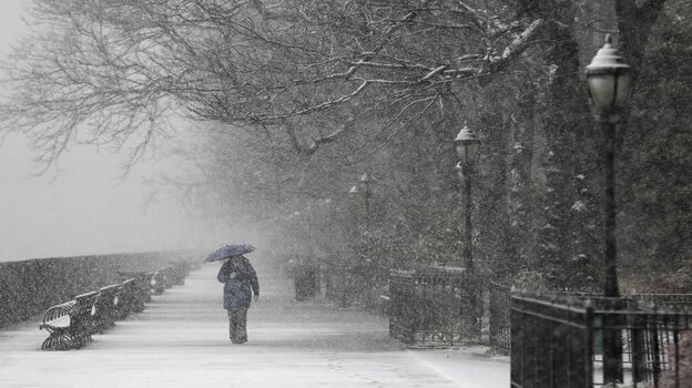 A person walks on a deserted walkway on a snowy morning in New York City on Tuesday. People who live along the East Coast and the Appalachians woke up to snow Tuesday, forcing school closings and closed roads.