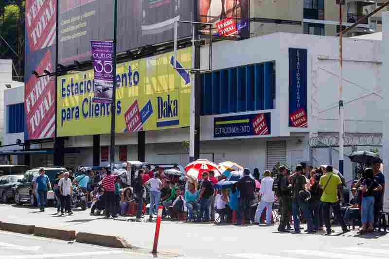 Venezuelans line up outside a branch of an electronics store in Caracas on Nov. 11. President Maduro ordered electronics stores to lower their prices as a measure against inflation, causing masses of people to queue outside stores in hopes of grabbing bargains.
