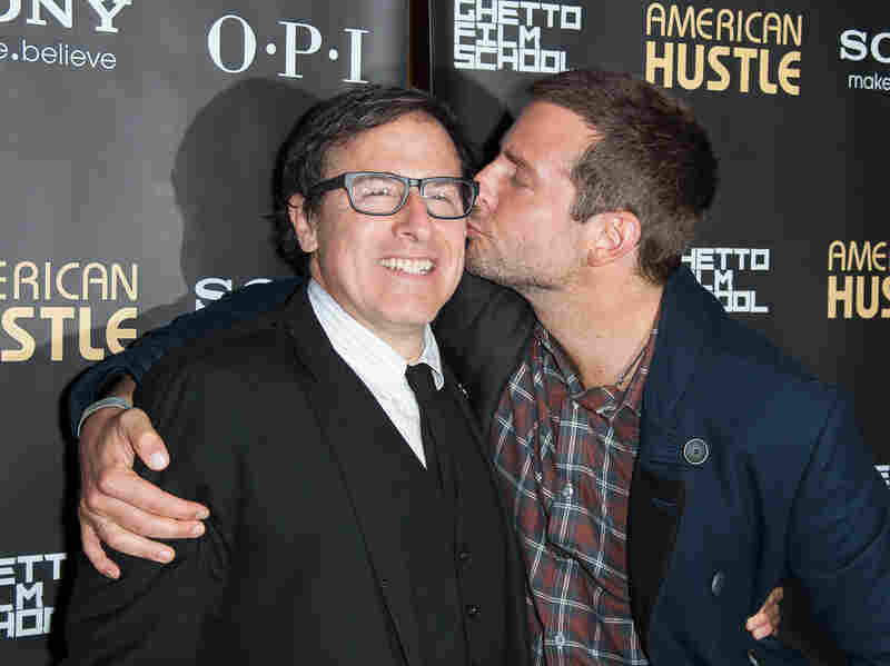 Russell (left) shares a moment with Bradley Cooper at an American Hustle screening. Russell also directed Cooper in last year's Silver Linings Playbook.