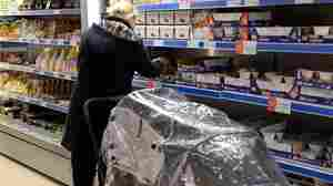"""A customer scans the shelves at Community Shop, the U.K.'s first """"social supermarket."""" The discount grocery stores are growing in popularity across Europe and are open exclusively to those in need."""