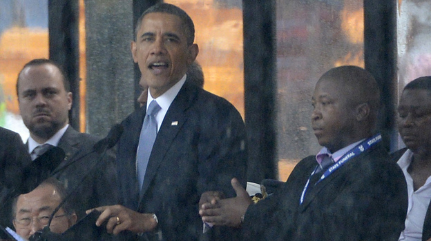 As President Obama and other world leaders spoke Tuesday in Johannesburg at a memorial for Nelson Mandela, a man stood nearby and appeared to be doing sign language interpretation. Many in the deaf community are outraged because the man appeared to be faking. (AFP/Getty Images)