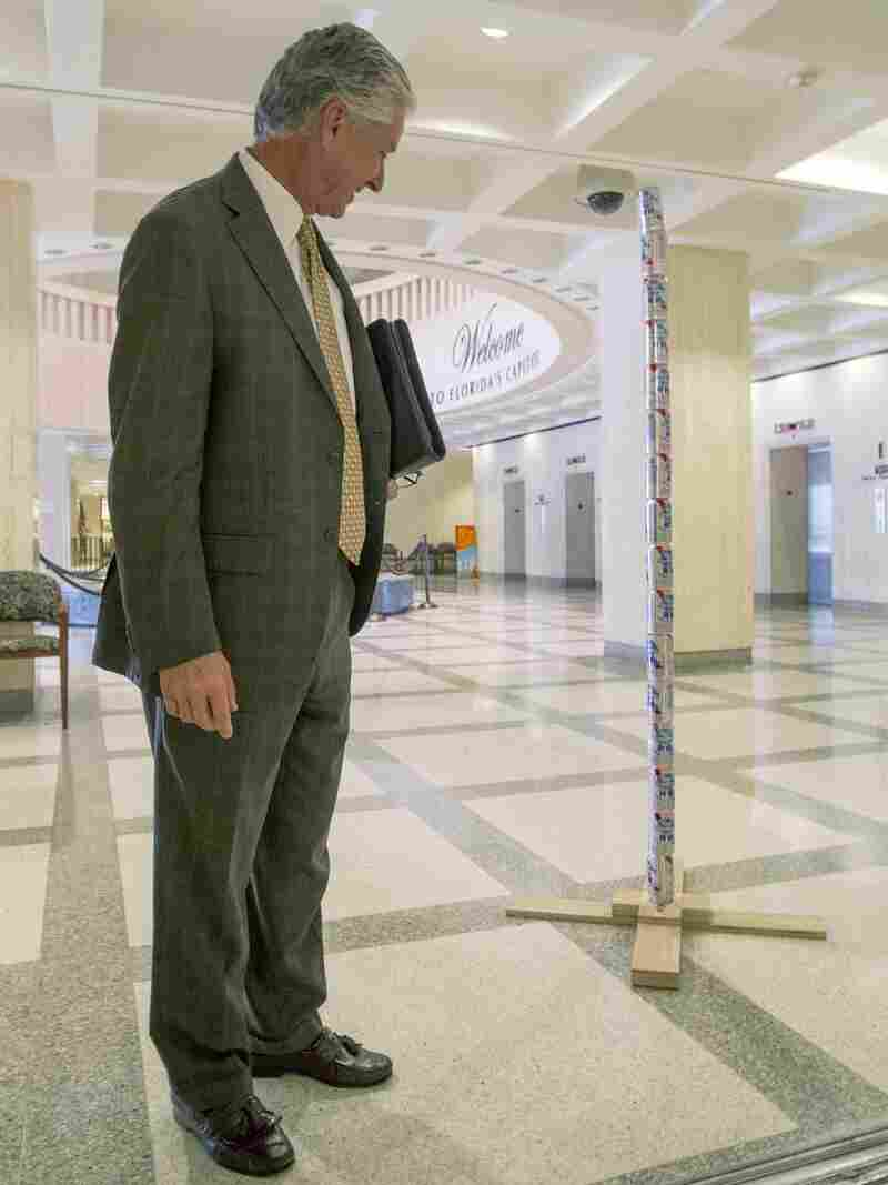 Florida lobbyist Keith Arnold stops to look at Chaz Stevens' Festivus pole made out of beer cans in the rotunda of the Florida Capitol in Tallahassee.