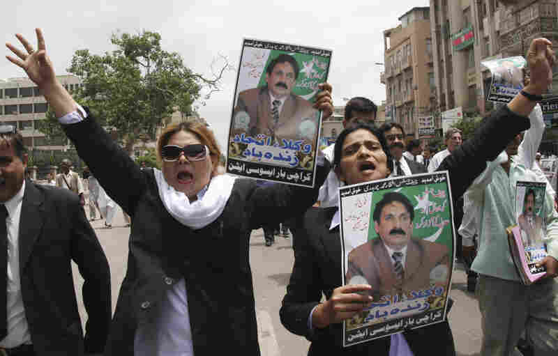 Pakistani lawyers hold portraits of Chaudhry as they chant slogans against then-President Pervez Musharraf during a 2008 rally in Karachi demanding the restoration of all deposed judges.