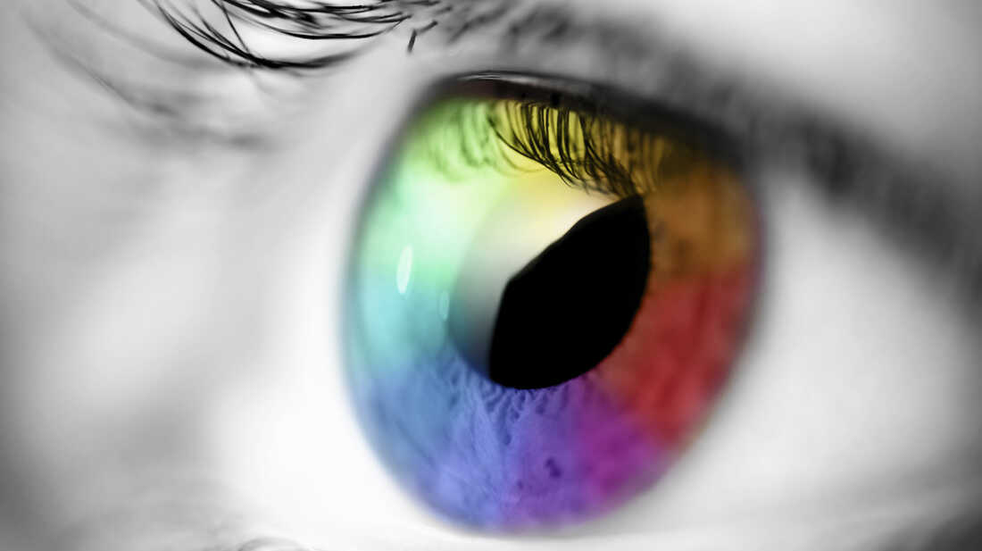Black and white photo of an eye; the iris is colored in multiple hues.