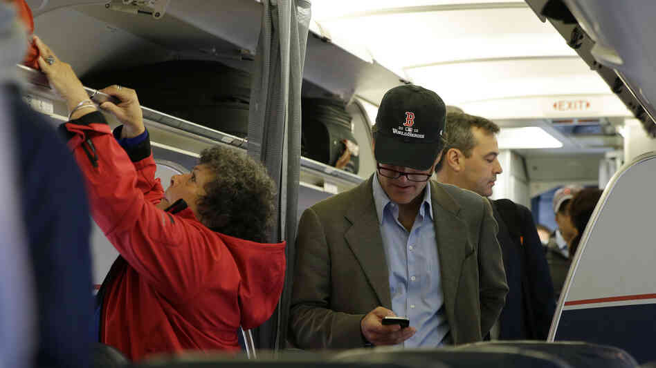 A passenger checks his cellphone while boarding a flight in Boston. The Federal Communications Commission is proposing new rules to allow using cellphones for data and voice calls during airline flights.