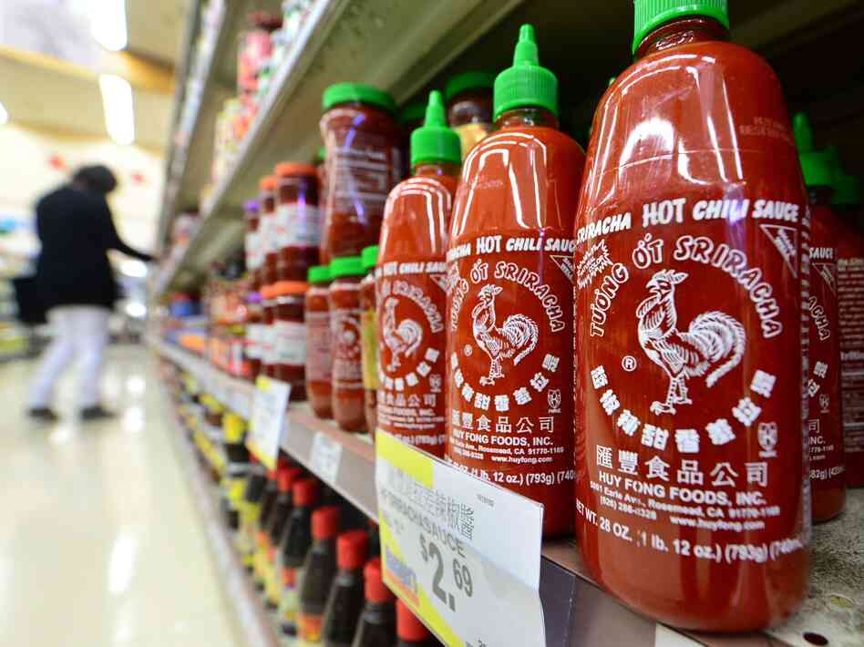 Bottles of Sriracha chili sauce on the shelves of a supermarket