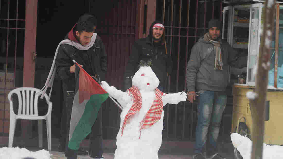 Palestinians build a snowman in the West Bank city of Ramallah on Friday.