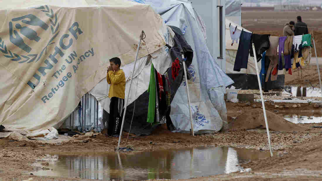 A Syrian refugee plays Thursday after heavy rain at the Zaatari refugee camp in Jordan.