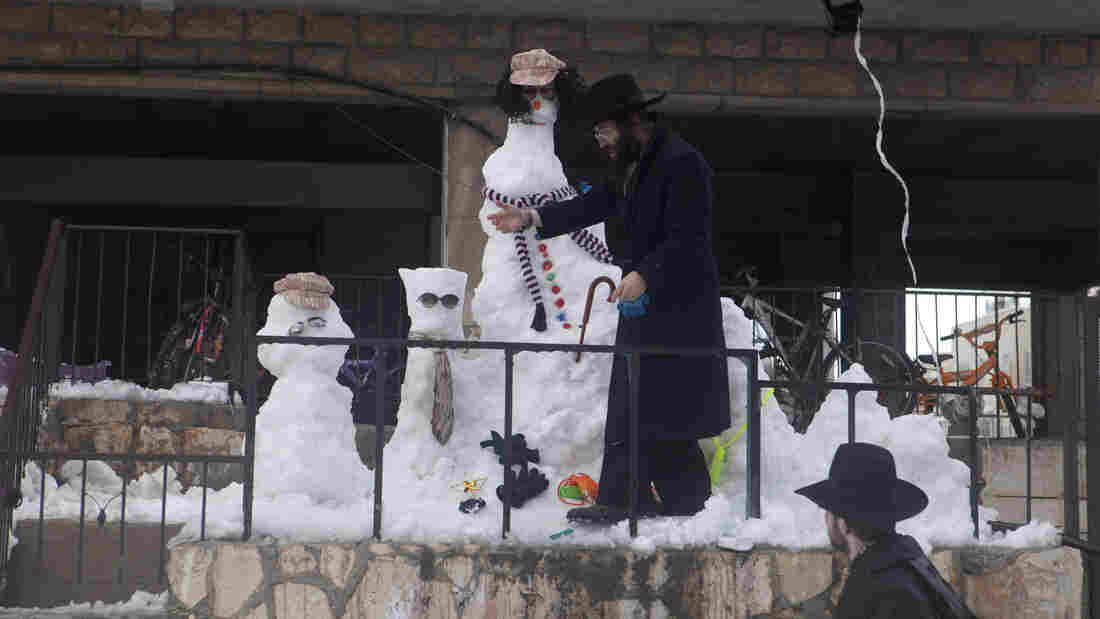 An Ultra Orthodox Jewish man builds a snowman on Friday in Jerusalem.