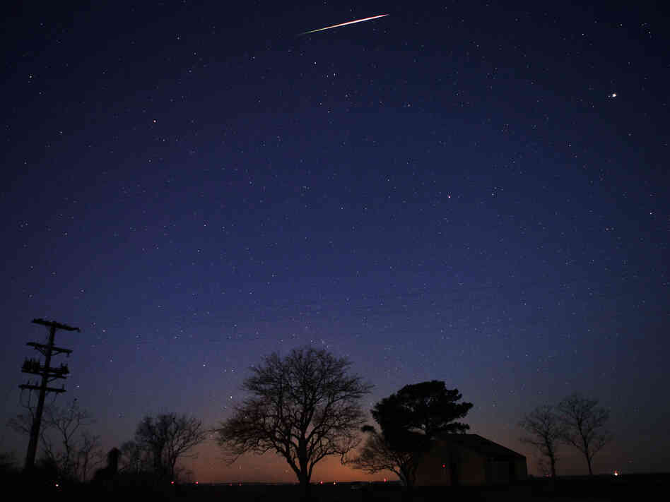A Geminid meteor streaks across the sky early Friday n