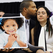 """Jimmy Greene holds a picture of his daughter, Ana, as he kisses his wife Nelba Márquez-Greene, at a January news conference in Newtown, Conn. They try to remember the good days with their daughter. """"It is what brings me great comfort and great joy,"""" Márquez-Greene says."""