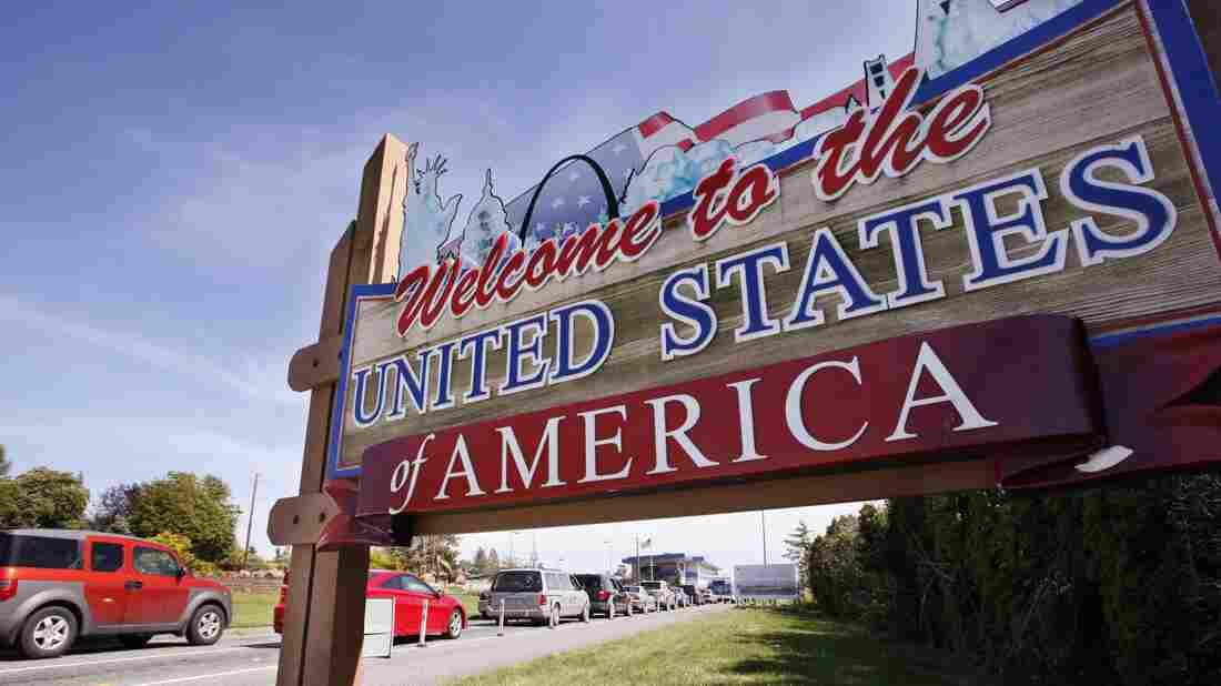 Cars entering the U.S. pass a welcome sign at the border crossing between the U.S. and Canada, in Blaine, Wash.