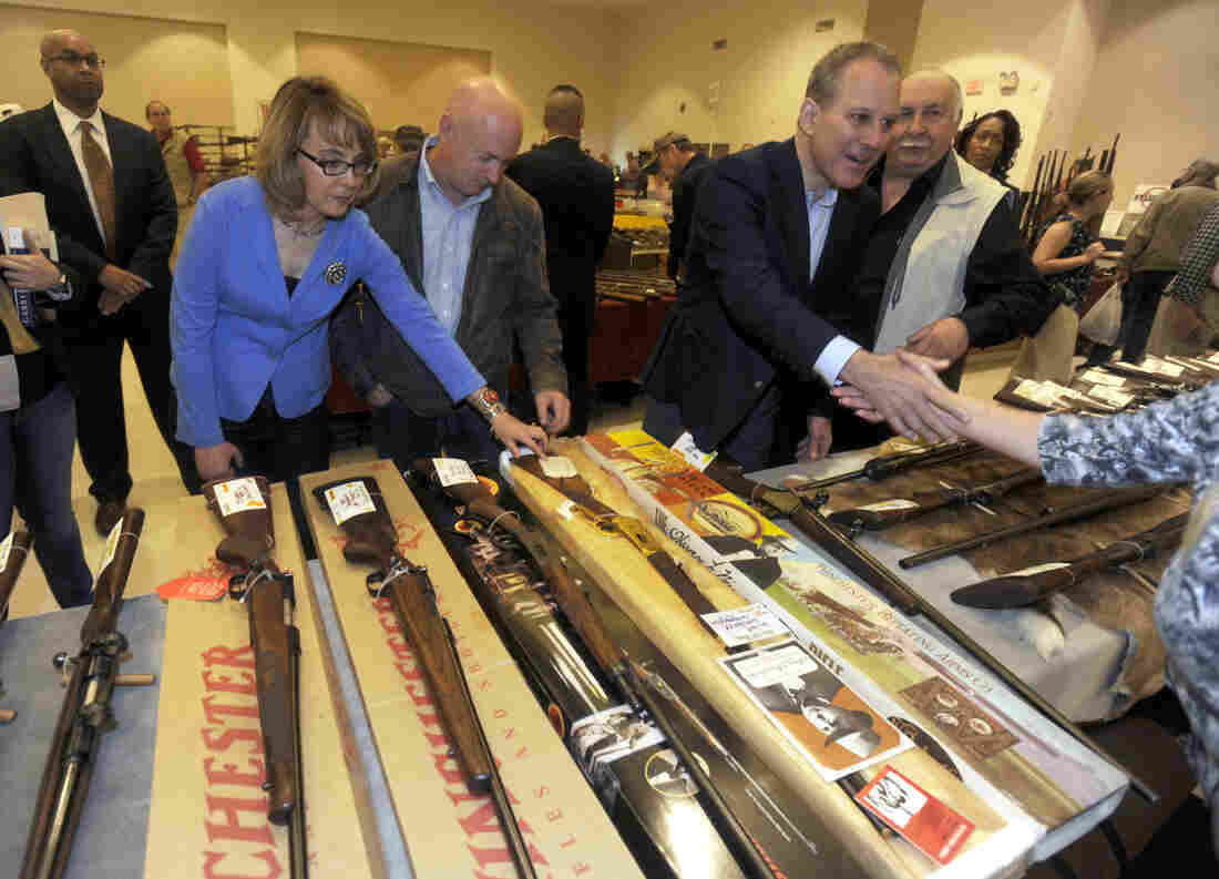 Former Rep. Gabby Giffords and her husband, Mark Kelly, at a gun show in Saratoga Springs, N.Y., in October. Giffords was shot in the head in a 2011 mass shooting in Tucson. She and Kelly have since founded a political action committee to push for tougher gun laws.