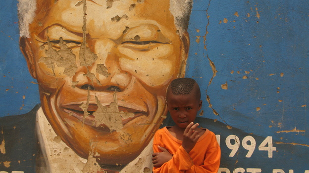 A South African boy stands in front of a mural of Nelson Mandela in Soweto, South Africa, earlier this month. (Veronique Tadjo for NPR)