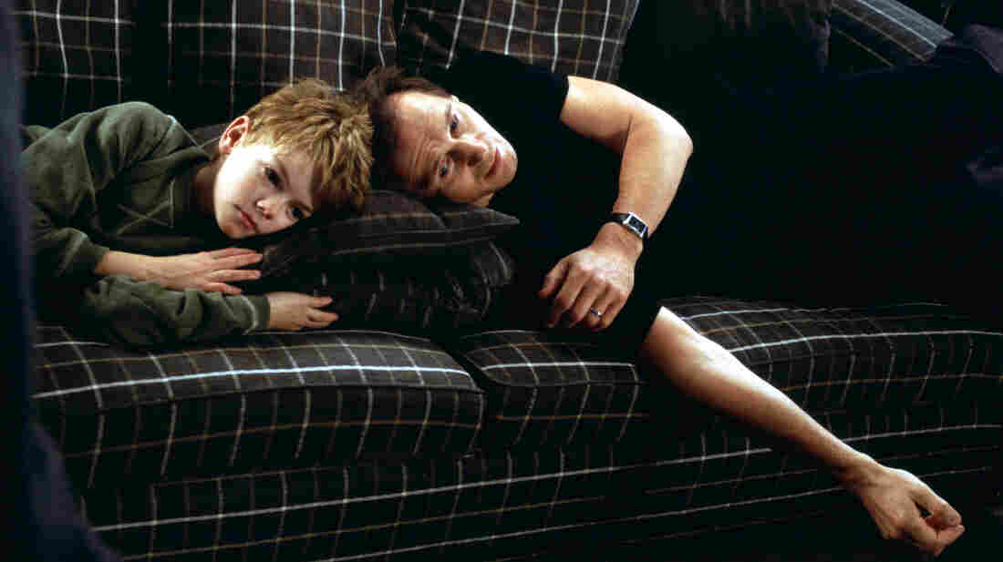 Sam (Thomas Brodie-Sangster) and his stepfather Daniel watch the movie Titanic to try to cure their love woes.