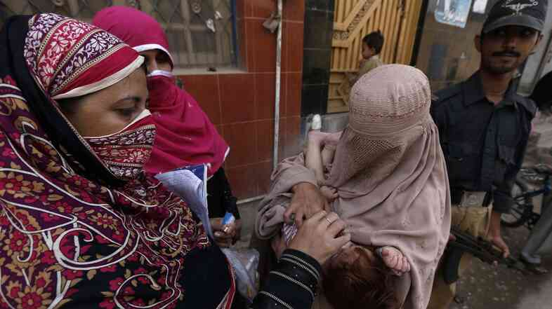 A polio worker vaccinates a child in Khyber-Pakhtunkhwa province, Pakistan, in October.