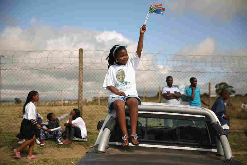 A girl waves a flag after former Mandela's funeral cortege moved past cheering crowds on its way to his family's rural home on Saturday in Mthatha, South Africa.