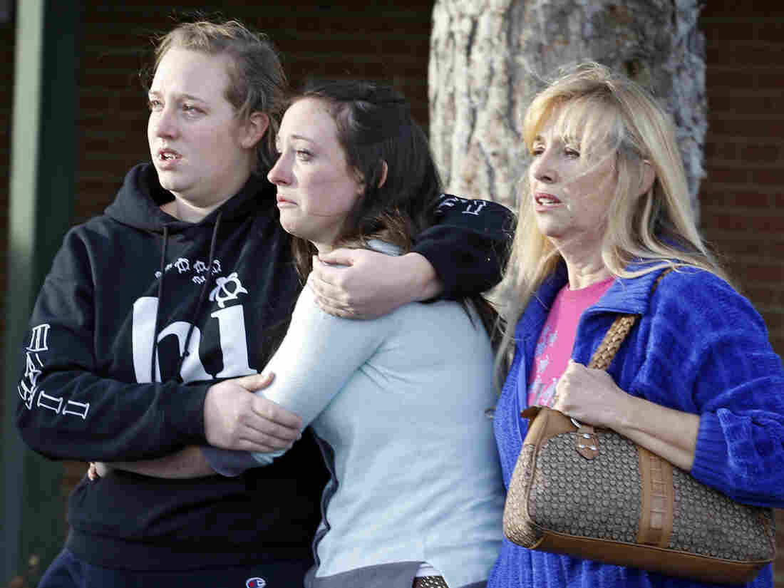 Senior Jenni Meyers, center, is hugged by her sister Mary as they leave a church with their mother Julie after they were reunited after a shooting at nearby Arapahoe High School in Centennial, Colo.