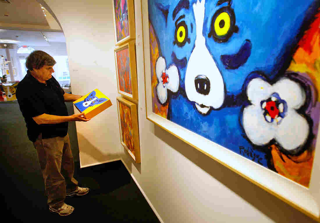 """Artist George Rodrigue looks at one painting of the three-canvas series titled """"Three Coins in the Fountain"""" in 2010."""