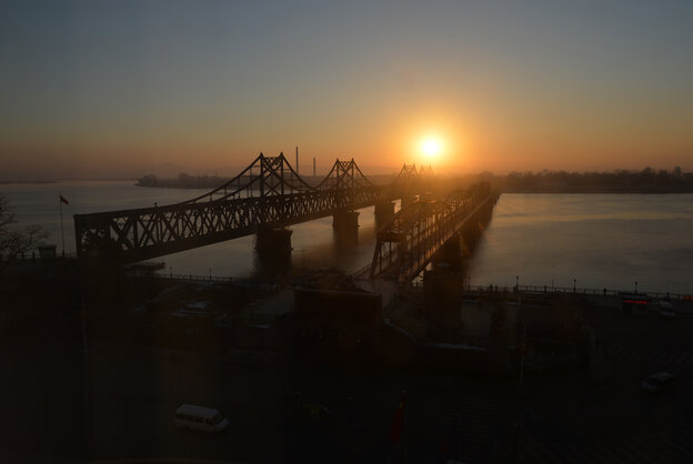 The sun rises over the Sino-Korean Friendship Bridge, which spans the Yalu River and leads into North Korea (background), at the Chinese border town of Dandong.