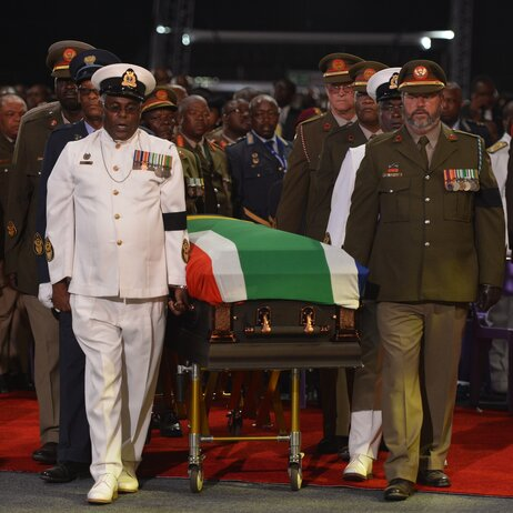 The casket of Nelson Mandela is escorted to the funeral ceremony in Qunu.