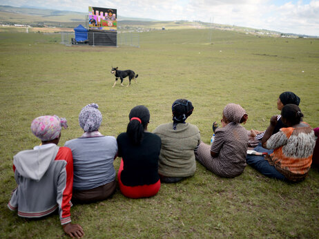 People watch the big screens at the site where Nelson Mandela will be buried on his family's property in his childhood village.