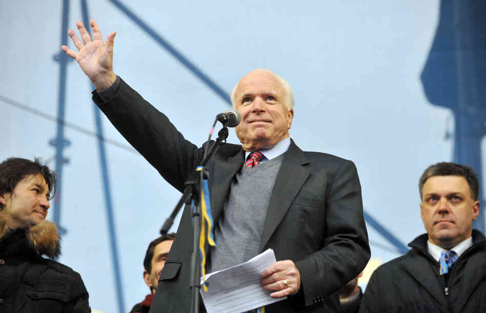 Sen. John McCain waves to protestors during a mass rally of the opposition at Independence Square in Kiev on Sunday.