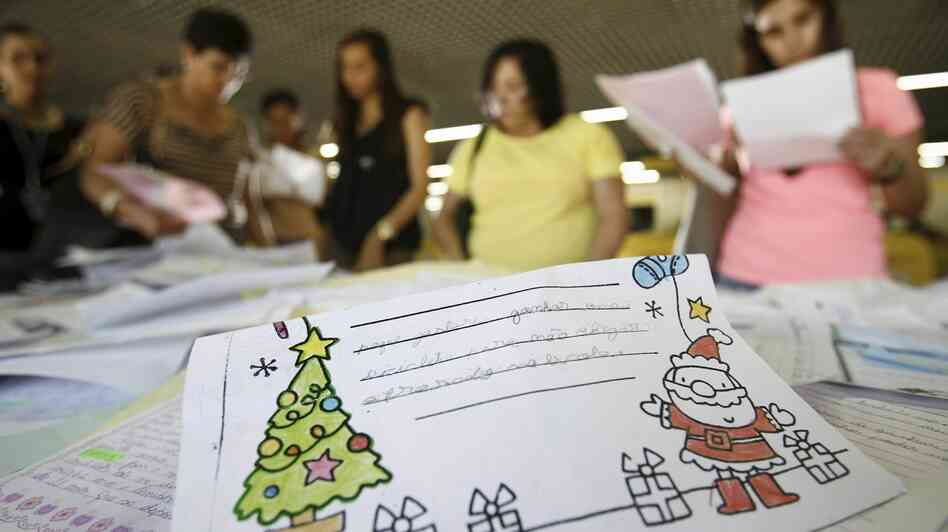 Volunteers look through children's letters to Santa at a post office in Salvador in n