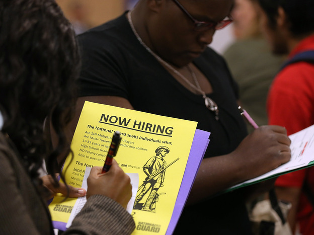 Attendees of a job fair in California in October fill out paperwork.