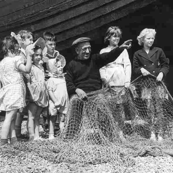 Fisherman Teddy Head tells a story to a group of children while mending his nets in Hastings in 1952. The fishermen of Hastings are tightknit; fathers, brothers and sons work together in rugged boats no more than about 30 feet long. Some families in Hastings have worked this way for centuries.