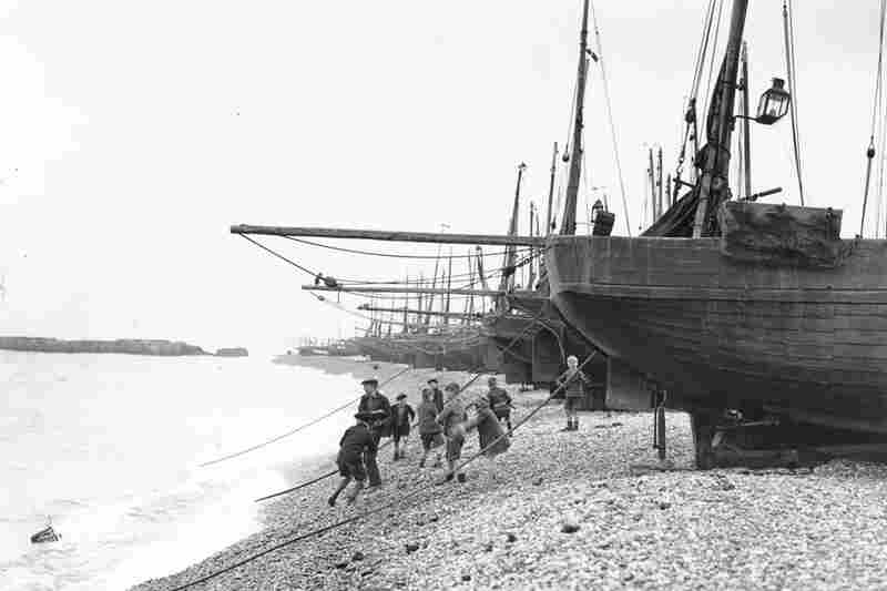 Children throw stones into the sea at Hastings in 1931.