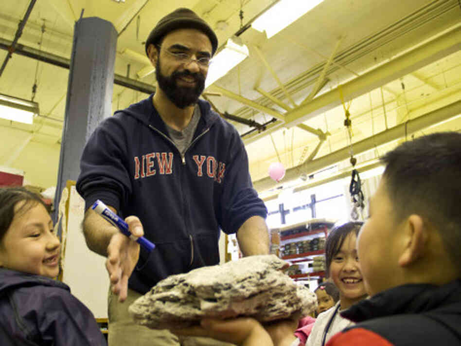Teacher Aaron Martin and his class examine lava rocks before making their own at the Mission Science Workshop.