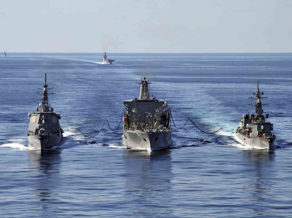 In this Dec. 5, 2010 file photo released by U.S. Navy, USNS Tippecanoe, center, refuels Japan Maritime Self-Defense Force
