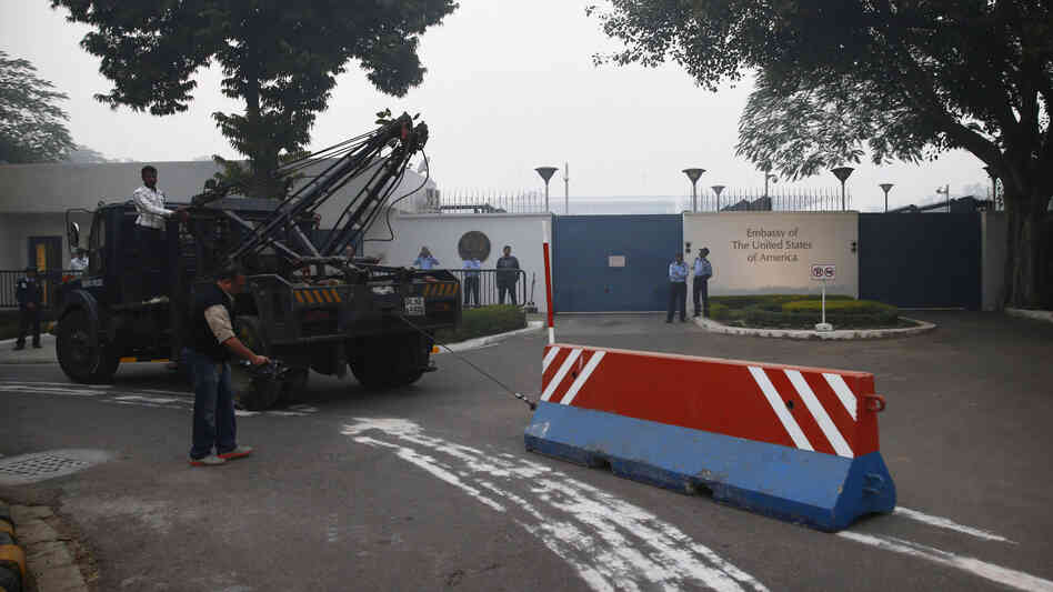 Indian workers remove Tuesday a barricade that had been erected as a safety measure outside the main entrance of U.S. Embassy in New Delhi. The move follows the arrest of an Indian diplomat in New York.