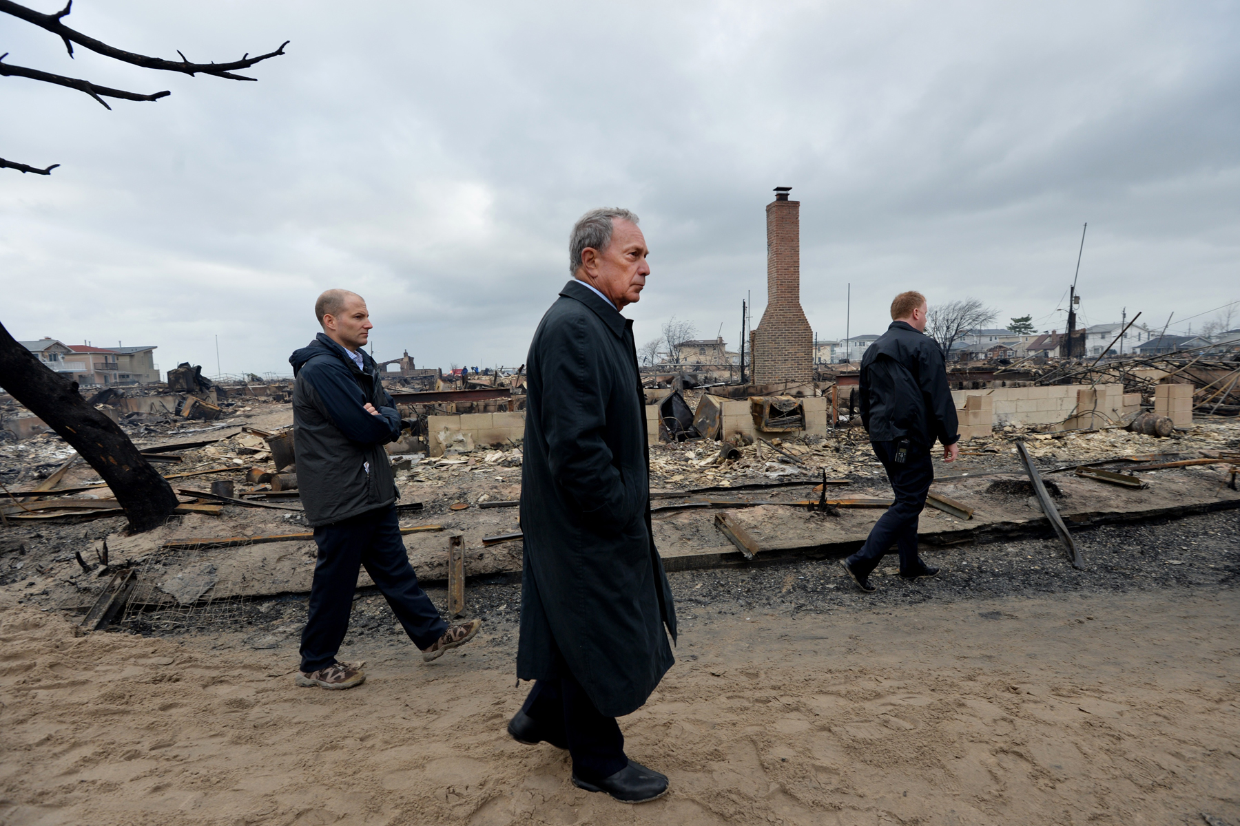 Bloomberg (center) views the Breezy Point area of Queens on Oct. 30, 2012, after fire destroyed about 80 homes as a result of Hurricane Sandy, which hit the area a day earlier.